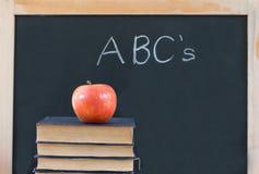 Onderwijs: ABC op bord met appel & boeken Stock Afbeeldingen