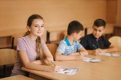Onderwijs, basisschool Het leren en mensenconcept - groep die schooljonge geitjes met pennen en notitieboekjes test binnen schrij royalty-vrije stock afbeeldingen