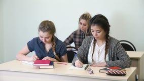 Onderwijs die de nota van de de klasgenoothulp van de schooltest bestuderen stock videobeelden