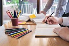 Onderwijs en schoolconcept, studentencampus of klasgenoten die tutorings de achterstand inlopende vriend voor een test of een exa royalty-vrije stock afbeelding