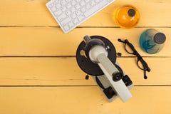 Onderwijs en wetenschapsconcept - microscoop, computertoetsenbord, oogglazen en chemische vloeistoffen op het gele bureau in audi royalty-vrije stock foto