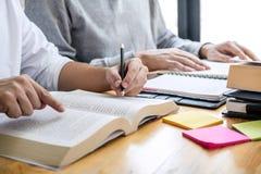 Onderwijs, het onderwijs, het leren concept De de middelbare schoolstudenten of klasgenoten groeperen privé-leraar in bibliotheek stock fotografie