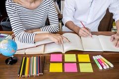 Onderwijs, het onderwijs, het leren concept Twee van middelbare schoolstudenten of klasgenoten groepszitting in bibliotheek met h royalty-vrije stock afbeelding