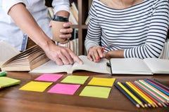 Onderwijs, het onderwijs, het leren concept Twee van middelbare schoolstudenten of klasgenoten groepszitting in bibliotheek met h royalty-vrije stock foto
