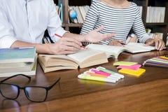 Onderwijs, het onderwijs, het leren concept Twee van middelbare schoolstudenten of klasgenoten groepszitting in bibliotheek met h stock afbeeldingen