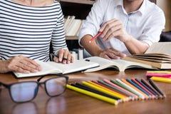 Onderwijs, het onderwijs, het leren concept Twee van middelbare schoolstudenten of klasgenoten groepszitting in bibliotheek met h royalty-vrije stock afbeeldingen