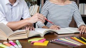 Onderwijs, het onderwijs, het leren concept Twee van middelbare schoolstudenten of klasgenoten groepszitting in bibliotheek met h royalty-vrije stock fotografie