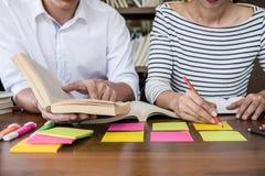 Onderwijs, het onderwijs, het leren concept Twee van middelbare schoolstudenten of klasgenoten groepszitting in bibliotheek met h stock fotografie
