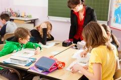 Onderwijs - Leerlingen en leraar die op school leren Stock Foto's