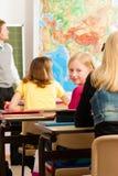 Onderwijs - Leraar met leerling in het schoolonderwijs Stock Foto
