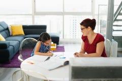Onderwijs met Mamma die Dochter helpen die Schoolthuiswerk thuis doen stock fotografie