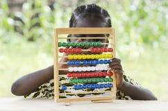 Onderwijs voor Afrika: Weinig Afrikaanse zitting van het schoolmeisje op school stock afbeeldingen