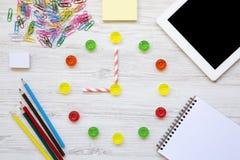 Onderwijsconcept, terug naar school Negen uren op horloge De klok van kleurrijk zoet suikergoed, toebehoren voor studie over wit  stock foto's