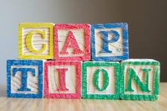 Onderwijsdiestuk speelgoed kubussen met brieven aan de TITEL van het vertoningswoord worden georganiseerd - het uitgeven meta-geg royalty-vrije stock foto's