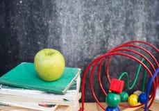 Onderwijssamenstelling met boeken, appel en zwart krijt Royalty-vrije Stock Afbeeldingen