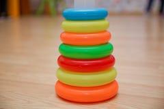 Onderwijsspeelgoed voor peuters, grijpende die ringen, op geel worden geïsoleerd Kleurrijke Piramide van Gestapelde Cirkelblokken stock foto's