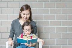 Onderwijst de close-up Aziatische moeder haar zoon om een boek op de geweven achtergrond van de steenbakstenen muur met exemplaar stock afbeeldingen