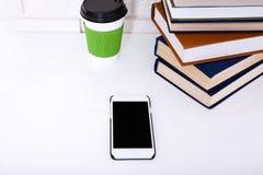 Onderwijswerkplaats met boeken, kop van koffie en mobilofoon op witte lijst dichtbij bakstenen muur Selectieve nadruk Stock Afbeeldingen