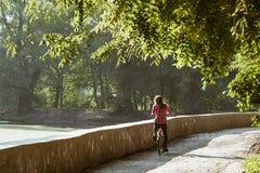 Onderworpen ecologisch fietsvervoer Jonge Kaukasische vrouw die op een landweg in een park dichtbij een meer berijden die oranje  stock afbeelding
