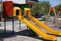 Onderzochte Speelplaats met Twee Kleurrijke Dia's en Schommeling Buurt Openbaar Park met Huizen Onveilige Recreatief royalty-vrije stock foto's