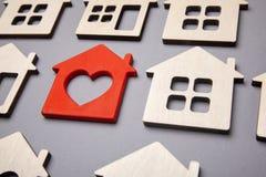 Onderzoek en selectie van huizen voor aankoop of huur Velen huisvesten en één rood hart stock fotografie