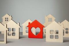Onderzoek en selectie van huizen voor aankoop of huur Velen huisvesten en één rood met hart royalty-vrije stock afbeeldingen