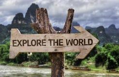 Onderzoek het Wereld houten teken met een bosachtergrond Stock Foto's