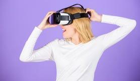 Onderzoek virtuele werkelijkheid Van de hoofdtelefoonglazen van de vrouwengreep vr de violette achtergrond Digitaal apparaat en m royalty-vrije stock afbeeldingen