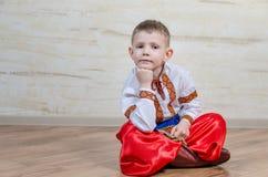 Onderzoekende jongen met traditioneel volkskostuum stock foto