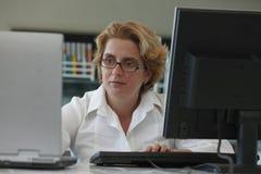 Onderzoeker die aan computers werkt Stock Afbeelding