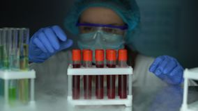 Onderzoeker die buizen met bloedserum nemen van koelkast, de analyse van stamcellen stock footage