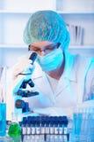 Onderzoeker die een microscoop in een laboratorium gebruikt stock foto's