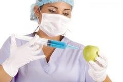 Onderzoeker die vloeistof in appel inspuit royalty-vrije stock afbeelding
