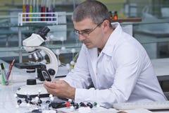 Onderzoeker die zijn mobiele telefoon controleert Stock Fotografie