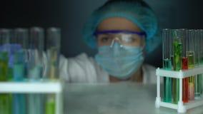 Onderzoeker het openen ijskast en het analyseren van blauwe transparante vloeistof in buis stock video
