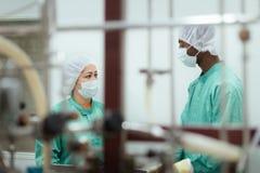 Onderzoekers die apparatuur in Biotech de industrie controleren Royalty-vrije Stock Foto's