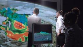 Onderzoekers die orkaan op monitor volgen stock afbeeldingen