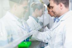 Onderzoekers die in wetenschapslaboratorium steekproeven voorbereiden stock afbeeldingen