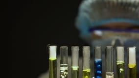 Onderzoekers druipende vloeistof in buizen met borrelende substanties, die reactie waarnemen stock video