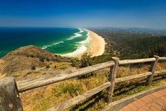 Ondes à la plage heurtée au phare de compartiment de Byron Images stock