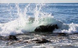 Ondes éclaboussant contre des roches Photo libre de droits