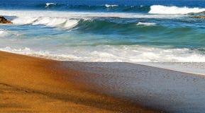 Ondes roulant sur le sable Photos stock
