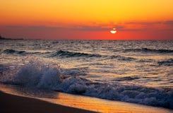 Ondes se cassant au coucher du soleil Photographie stock