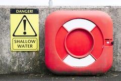 Ondiep waterteken en de rode boei van de het levensveiligheid bij havenmuur royalty-vrije stock foto