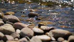 Ondiepe steenachtige kust die door glans en morserijwater wordt gewassen op een zonnige dag stock footage
