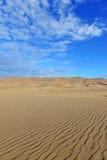 Ondinhas em dunas de areia e no céu azul Fotografia de Stock