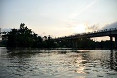 Ondinhas na água, ponte através da floresta no fundo, com o Sun que pendura baixo Imagens de Stock