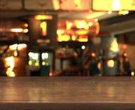 Onduidelijk beeld bokeh achtergrond met lege houten lijstbovenkant in nachtkoffie stock foto