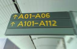 Onduidelijk beeldbeeld van aanwijzingssignalen in internationale die luchthaven als achtergrond wordt gebruikt Stock Afbeelding