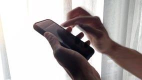 Onduidelijk beeldclose-up van mannelijke hand die smartphone gebruiken door het venster met wit gordijn en zonlichteffect royalty-vrije stock fotografie